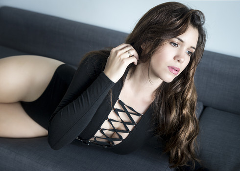 long hair brunette lying on the couch with beautiful decolletage candide moment photography