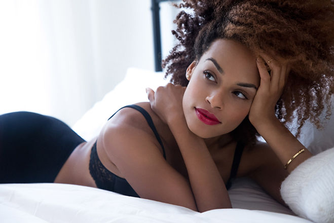 Boudoir portrait of a black woman lying on bed with afro hair and red lipstick nyc