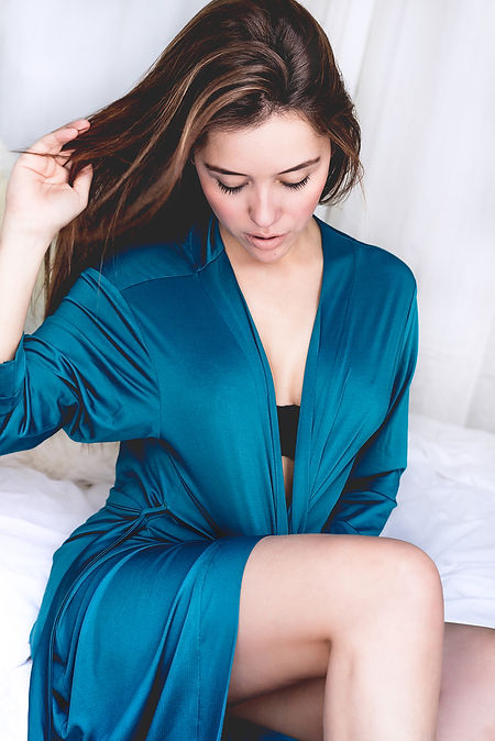 brunette sitting on a bed lifestyle loun