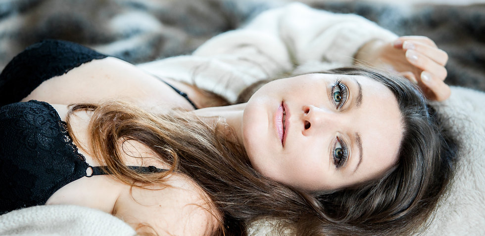 Boudoir and maternity photography studio portrait of a brunette with green eyes lying down on a bed