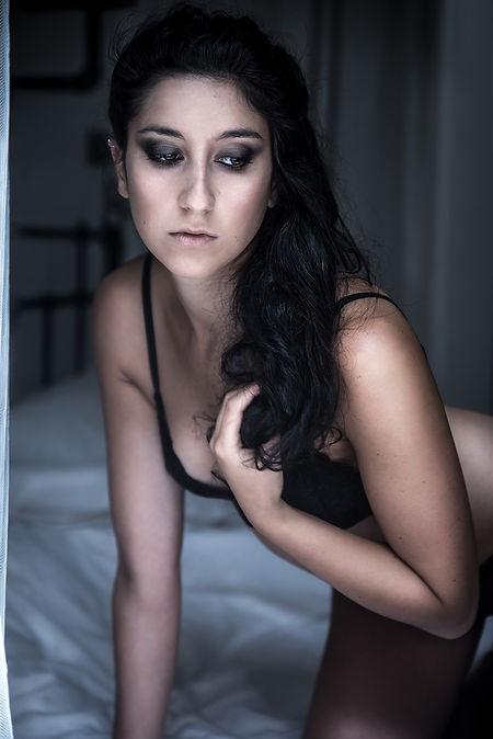 sensual brunette kneeling in front windo
