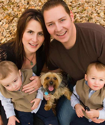Family with mother, father and 2 sons and yorkie dog sitting in leaves