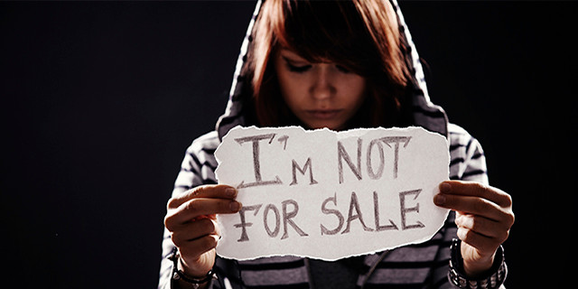 """Teen girl holding """"I'm not for sale"""" sign"""