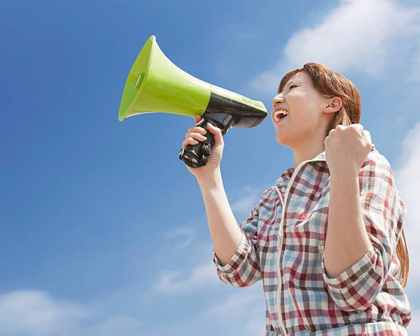 Close-up Of A Young Woman Shouting Through Megaphone Against Blue Sky