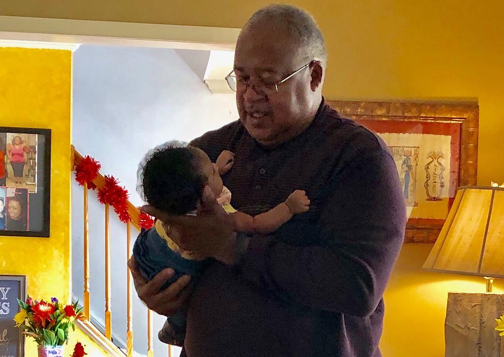 African American grandfather cradling granddaughter