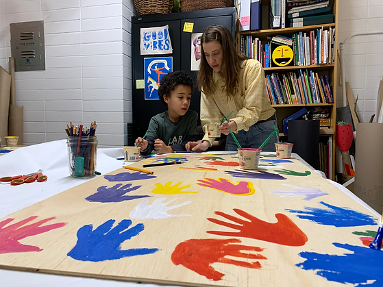 jamia painting hands with boy.png