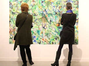 photo of 2 people looking at painting