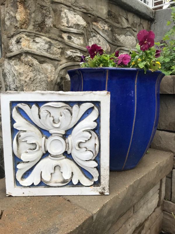 cast terra cotta block with flower motif, in the colors of white and blue.