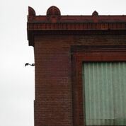 Salvaging the red terra cotta parapet caps, from St. Louis Mo.