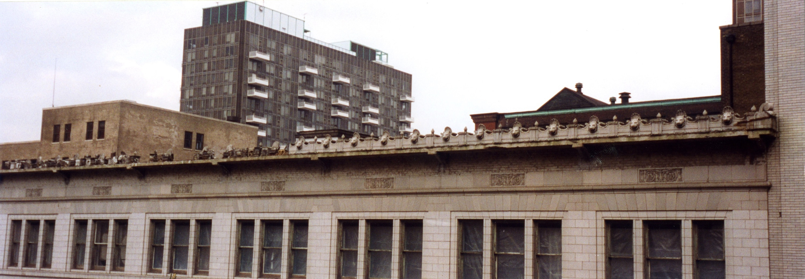 Photograph of the Marquette Annex Building under deconstruction, showing the lion heads that once rimmed the cornice.