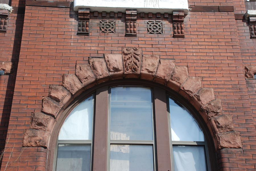Red sandstone arch over three windows, salvaged in pieces.