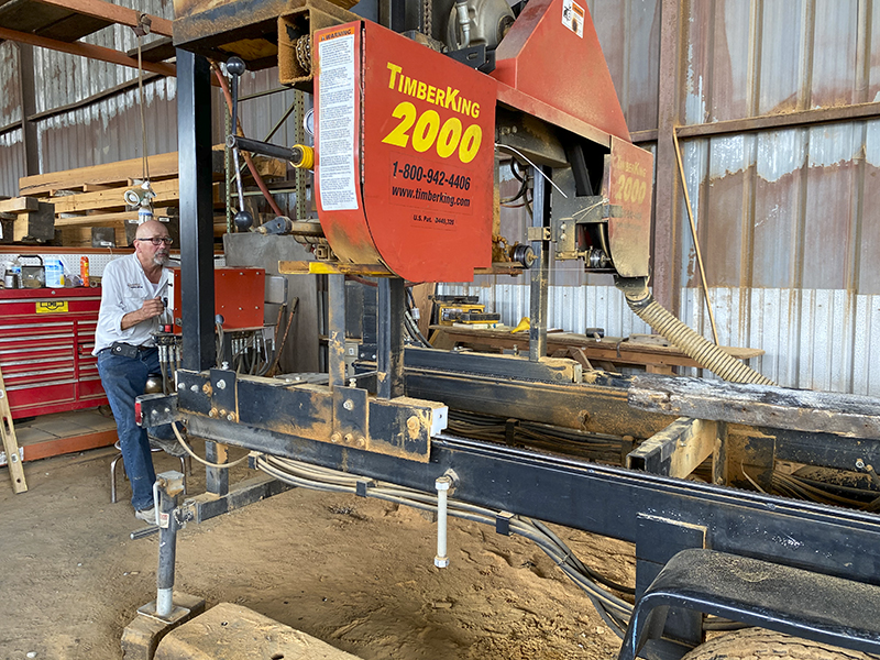 Bruce Gerrie about to operate the Timber King 2000 sawmill with a piece of long leaf yellow pine on the deck.