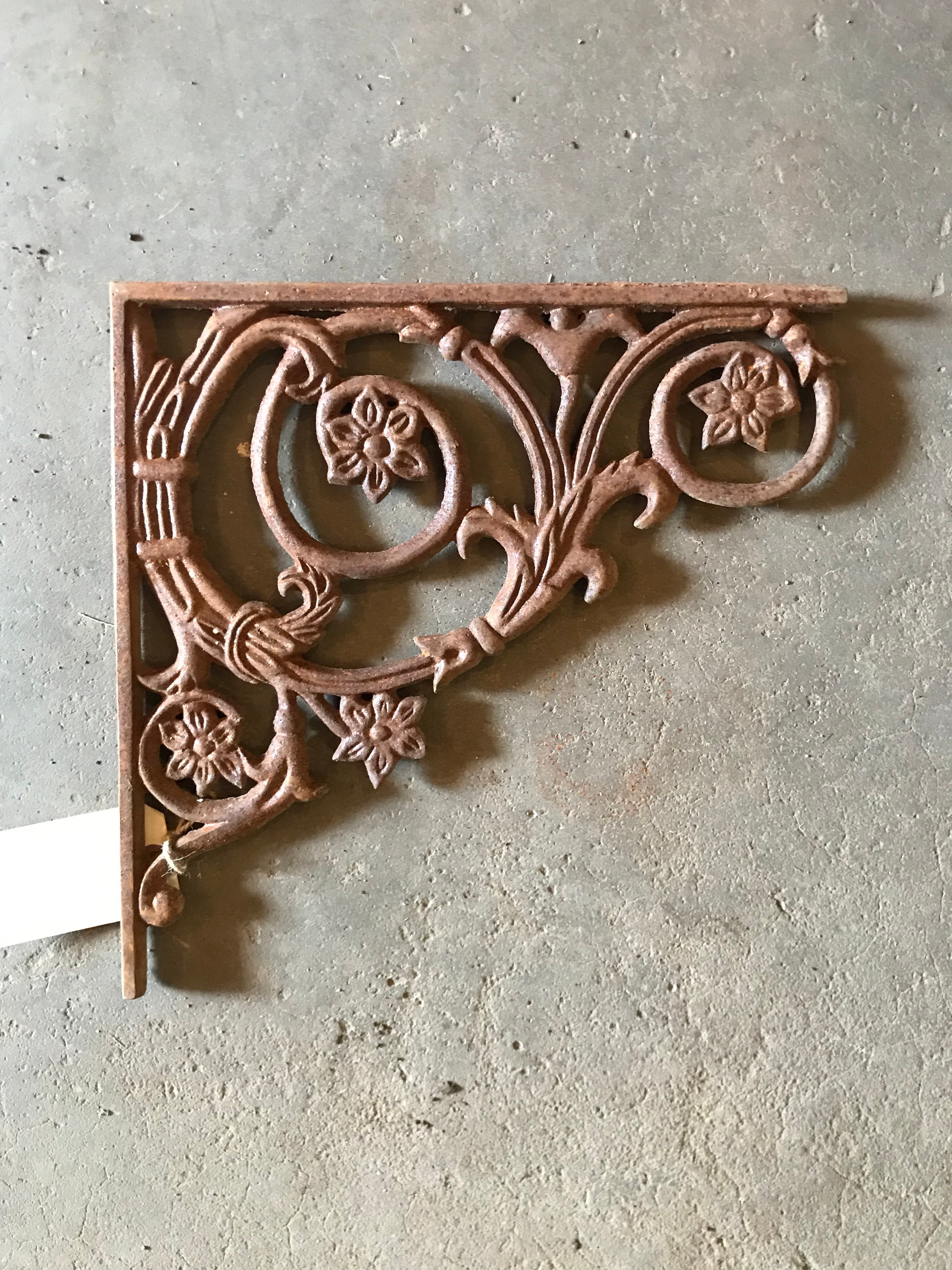 Cast iron replica bracket with vining flowers.
