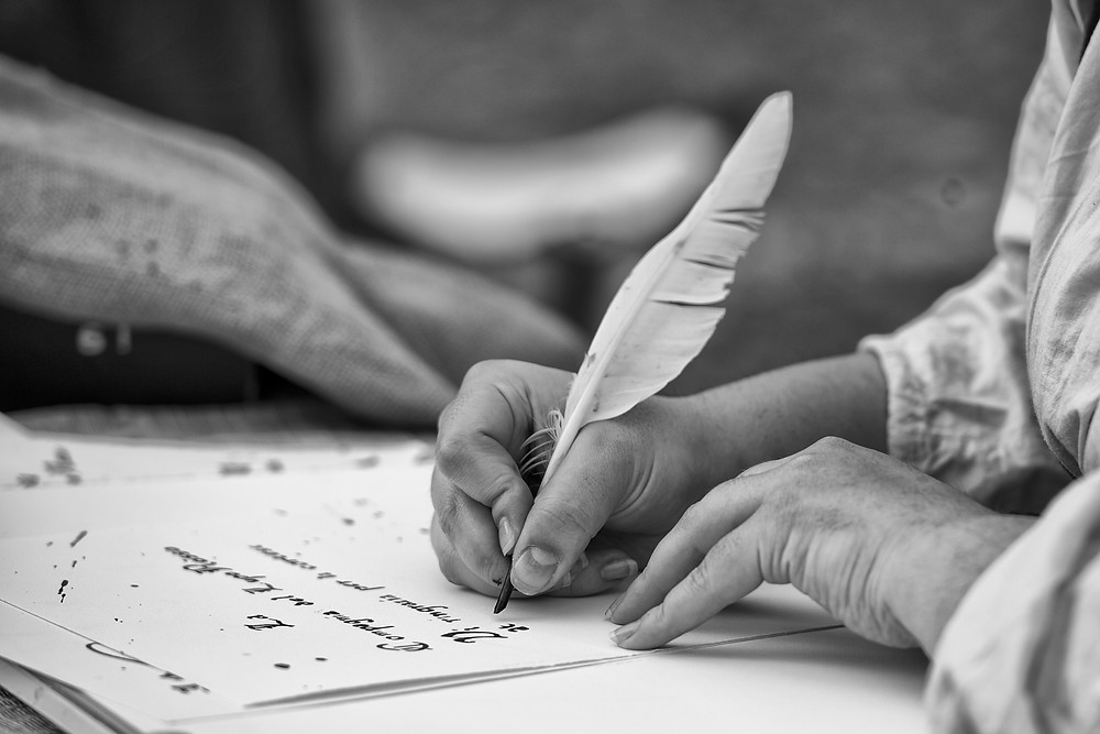 Man writing with quill on paper