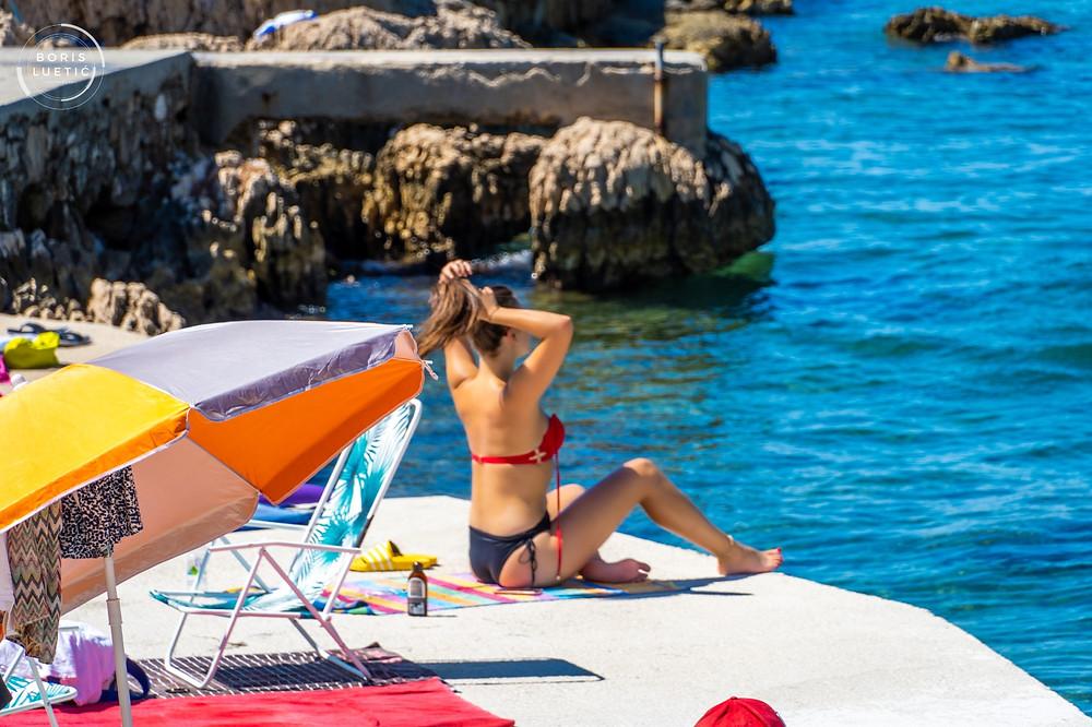 Attractive girl in bikini tanning on the Makarska beach