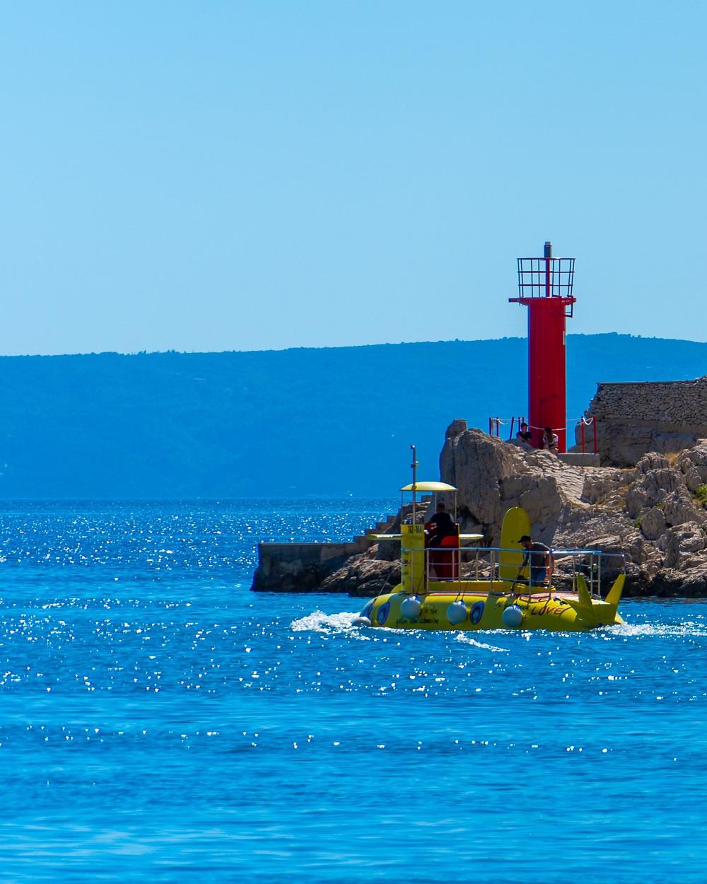 Red lighthouse and yellow semi submarine in Makarska
