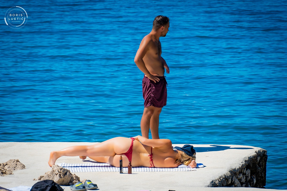 Men in shorts and a girl wearing red thong relaxing on Makarska beach