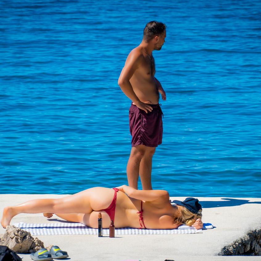 Couple lying on the beach and enjoying their holidays in Makarska