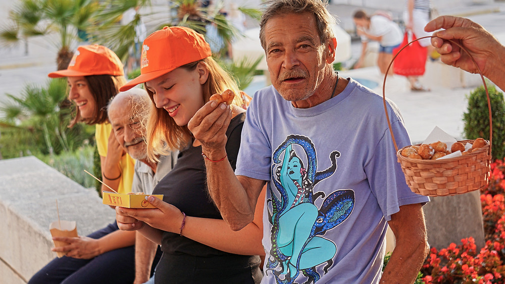 old and young people smiling while eating Dalmatian delicacies in Makarska