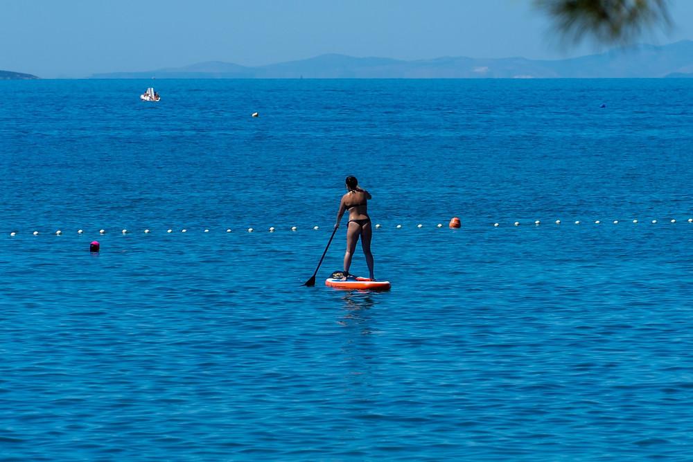 Girl in bikini paddle surfing along Makarska beach
