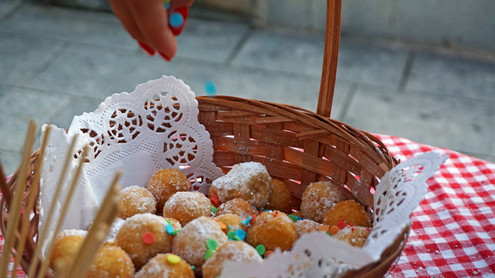 Croatian homemade fritters sprinkled with rainbow colored sprinkles in a wooden basket