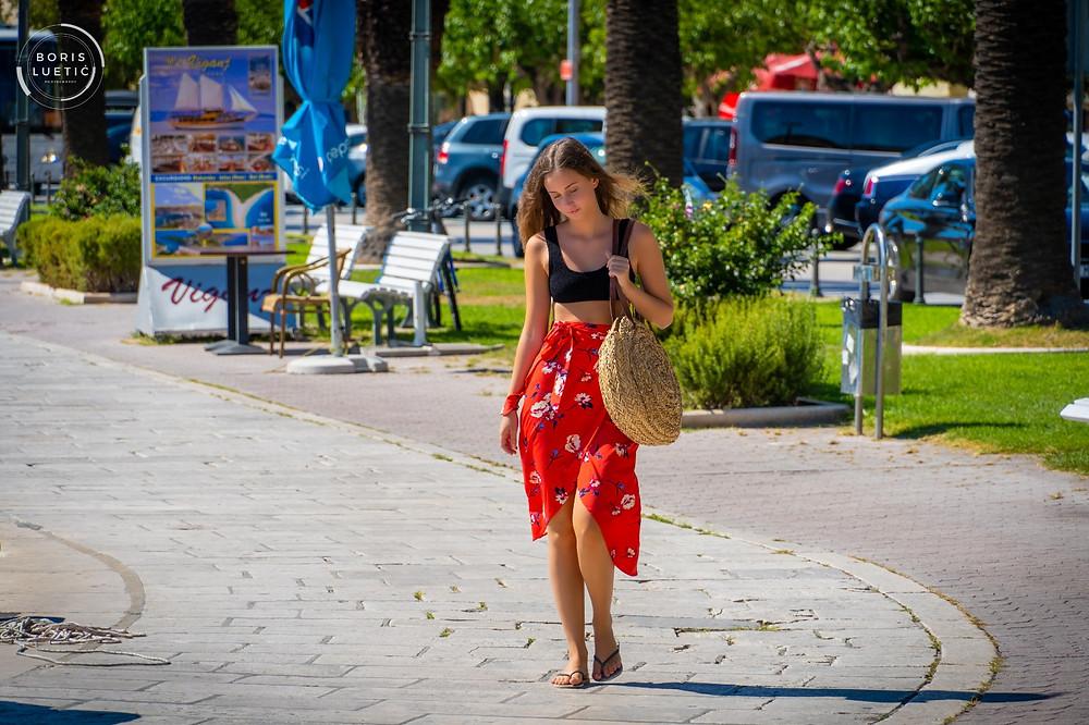 Beautiful girl walking around Makarska harbor