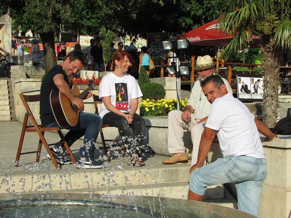 Guitarist entertaining his friends on Kacic Square in Makarska