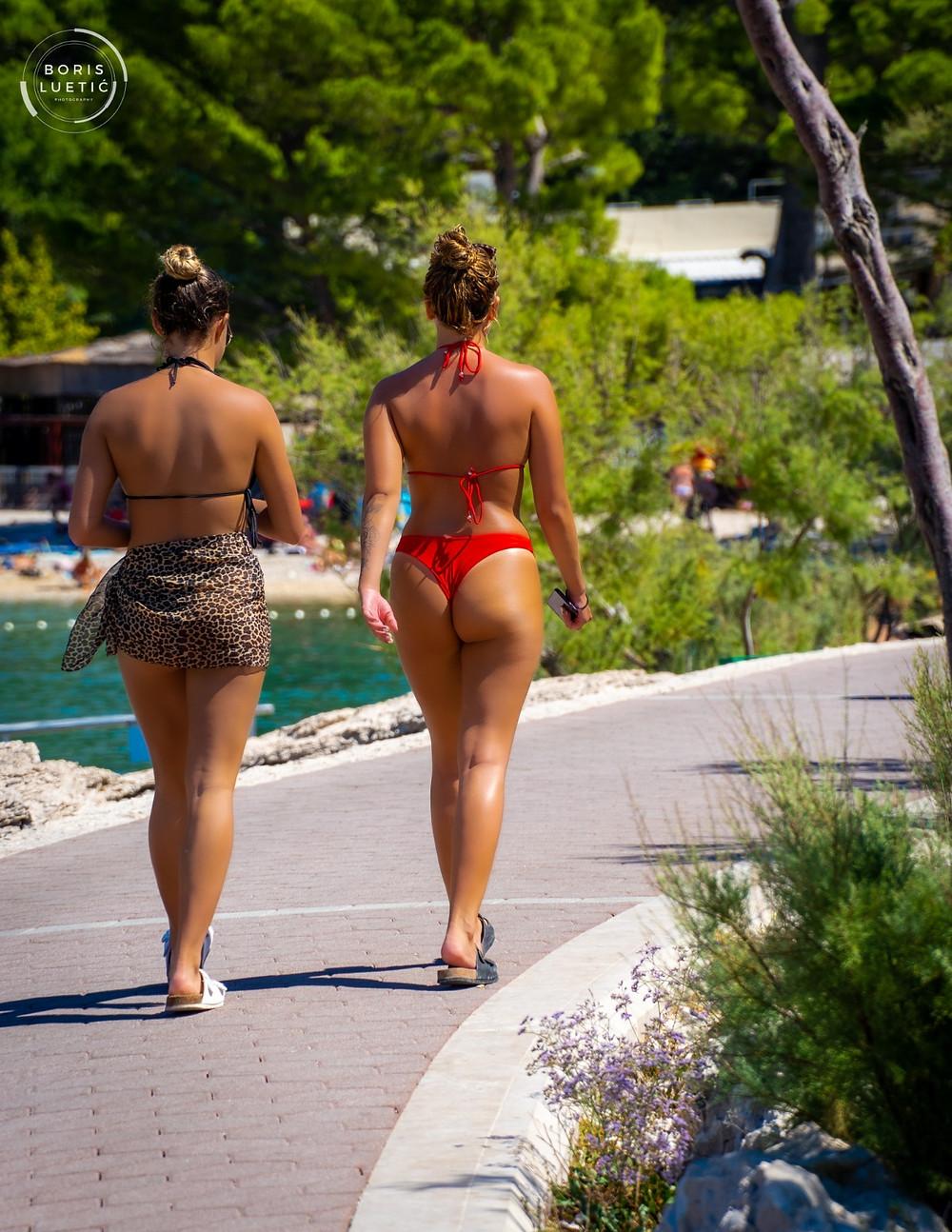 Attractive girls walking around Makarska beach, wearing summer clothes