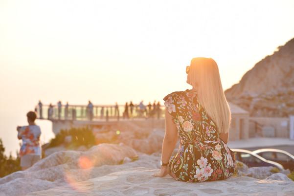 Blonde girl watching sunset at the Biokovo Skywalk in Makarska Riviera