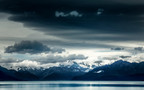 Storm clouds gather over Lake Pukaki. Aoraki (Mount Cook) shines in the distance