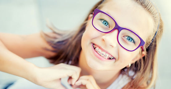 Young girl with braces gives a healthy smile.