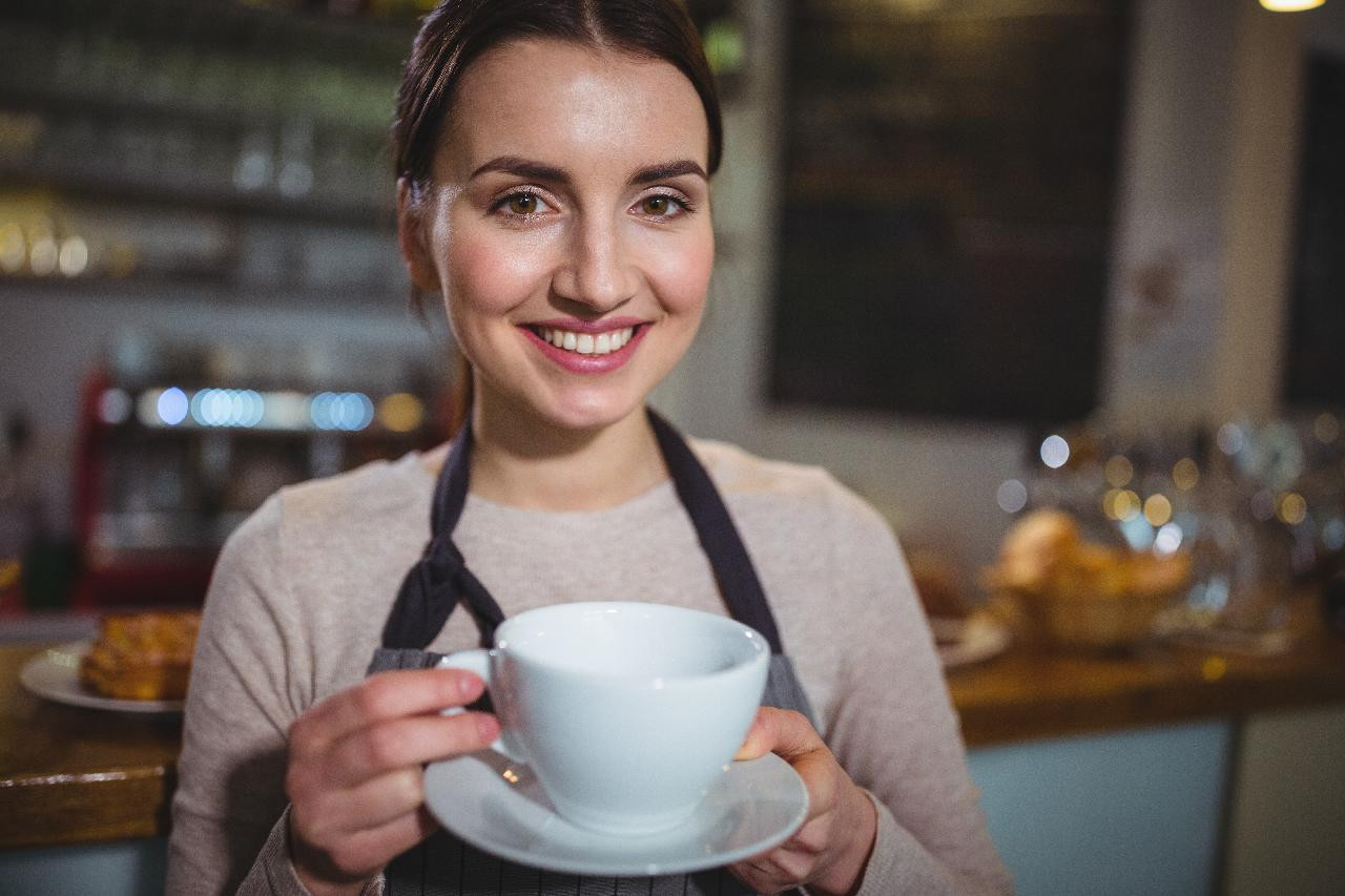 Nice girl offers you a cup of coffee and smiles at you