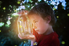 Boy looking into a jar of fireflies.jpg