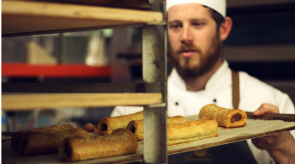 Baker putting sausage rolls into the rack