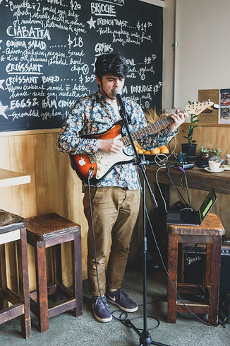 A young musician playing live music in the bakery.