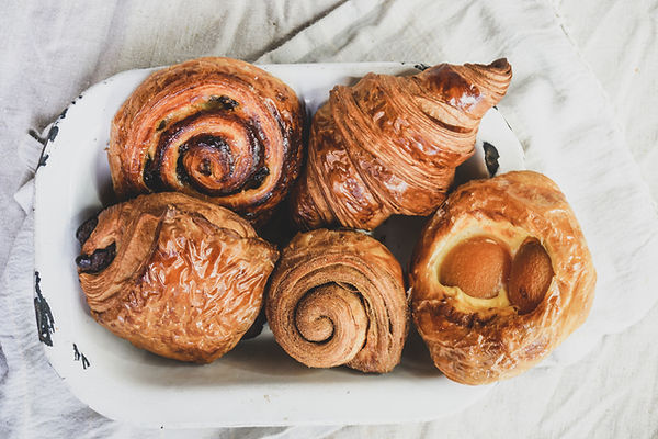 Selection of different pastries in a vintage bowl - croissant, pain au raisin, pain au chocolat, cinnamon bun and sweet apricot danish. All glased and shiny.