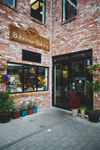 Entrance into the french bakery surounded by flowers and trees.