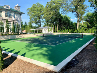 Sunken asphalt two-toned tennis court with stone retaining wall, stairs and landscaping.