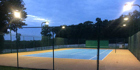 Court is all finished! Two-toned asphalt tennis court with practice board, green vinyl fencing and lighting system.