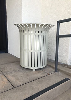 white metal litter receptacle trashcan sitting outdoors next to entrance