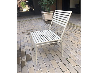 white metal dining chair sitting outside on brick