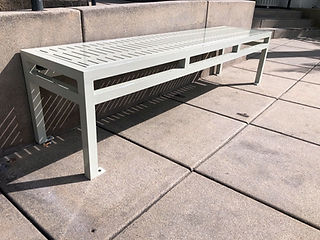 white metal bench sitting outside next to wall on sidewalk