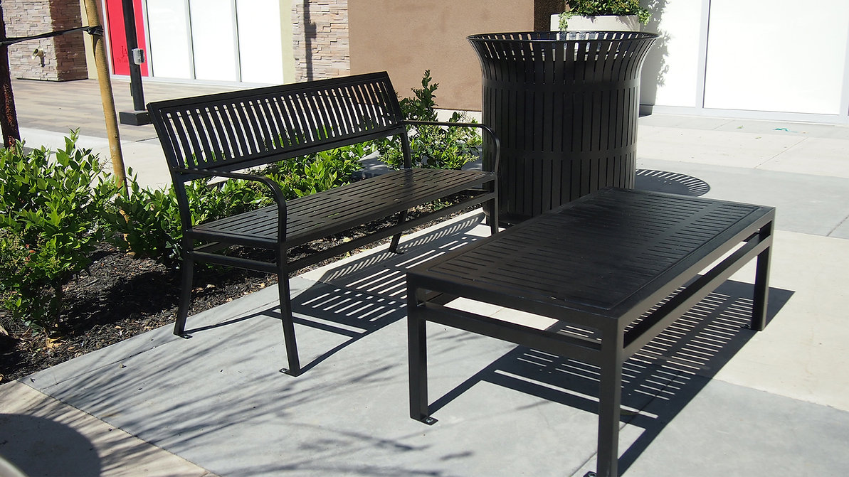 outdoor black metal bench, coffee table, and litter receptacle sitting outside on concrete