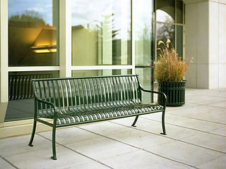metal bench sitting outdoors in front of windows