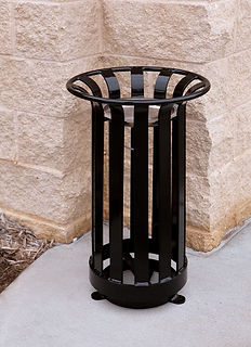 black metal ash urn outside in front of brick wall