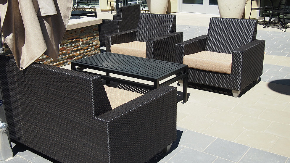 wicker furniture set with cushions sitting outdoors