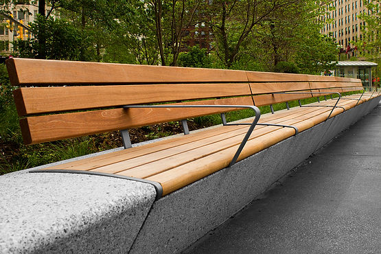 close up of wood bench with armrests outdoors
