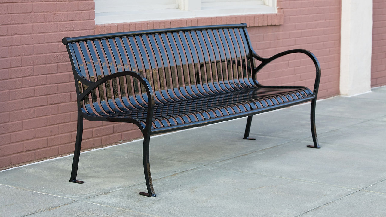 black metal bench sitting outside on concrete in front of brick wall