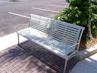 metal bench sitting outdoors on sidewalk
