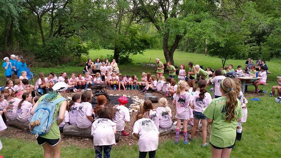 Photo of a group of Girl Scouts around a campfire ring.